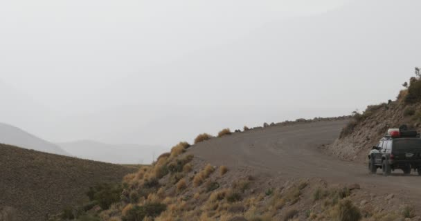 Van driving on gravel road in the surroundings of Domuyo Volcano, hides behind slope. Grey day, yellow grasslands on the slopes, mountains at background. Camera stays still. Neuquen, Patagonia