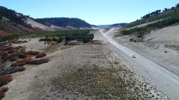 Letecká drone scéně štěrkové silnici a auto prochází v údolí řeky Litran. Barevná podzimní vegetace. Villa Pehuenia - Moquehue. Patagonia Argentina