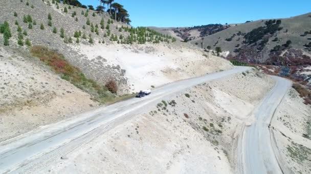 Letecká drone scéně karavan na štěrkové cestě v údolí řeky Litran. Barevná podzimní vegetace. Fotoaparát z vysokého úhlu pohledu na auto. Villa Pehuenia - Moquehue. Patagonia Argentina