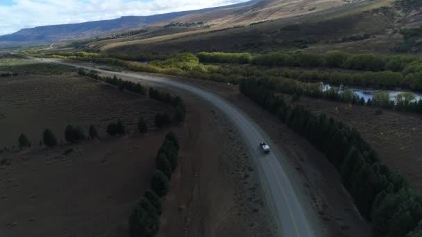 Letecká drone scéně stepi, hor, stromů a na silnici a van sledování a vozí přívěs s řekou Pulmari v pravé. Fotoaparát posunuli dál