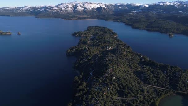 Drohnen-Szene einer Halbinsel mit Häusern in Villa pehuenia, moquehue, neuquen, patagonia argentina. Kamera bewegt sich auf einige Inseln im Aluminiumsee zu.