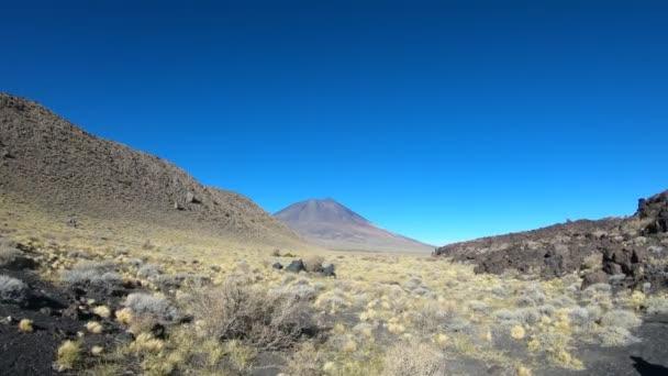 Stabilizovaný fotoaparát hnutí jít do strany na národní Park La Payunia v Malarge, Cuyo, Mendoza, Argentina. Payun Liso sopka na pozadí a stezky lávy na pravé straně