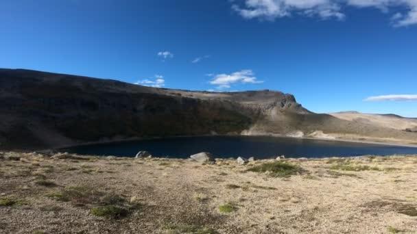 Stabilized camera movement going forward to a lagoon in Batea Mahuida volcanos crater at Villa Pehuenia, Moquehue, Neuquen, Patagonia Argentina. Big Mountain with steppe landscape.