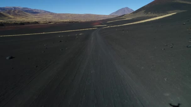 Aerial drone scene of La Payunia National Park in Malargue, Mendoza. Pampas Negras with black, red ground rocks from volcano and golden grasses pattern. Payun Liso volcano on background. Gravel road.