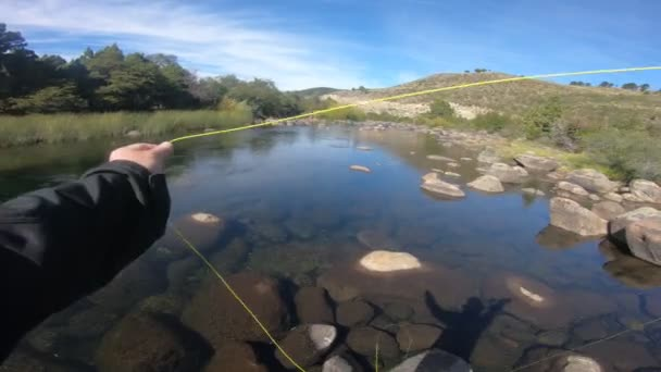 First person scene of man flyfishing casting in Pulmari river, in Neuquen, Patagonia Argentina on a sunny and windy day. River full of big rounded rocks.