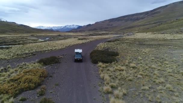 Letecká drone scéně The Andes hor v Mendoza, Cuyo Argentina. Patagonie stepní krajina. Fotoaparát bude zpětně přes štěrkové liduprázdné silnici sledování van s přívěsem, obytný vůz. Campanario horu se sněhem na pozadí. Zamračený den tmavě