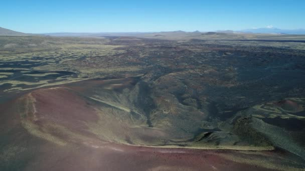 Aerial drone scene of La Payunia National Park in Malargue, Mendoza, Argentina. Old red volcano crater and bed of lava behind mountain peak. Background full of volcanos.