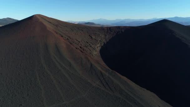 Letecká drone scéně tmavé, černé sopečného kráteru v la payunia národním parku, Malargue, mendoza, cuyo, Argentina. Fotoaparát, pohybující se nahoru. Cesta na horském svahu. Andes hor v pozadí