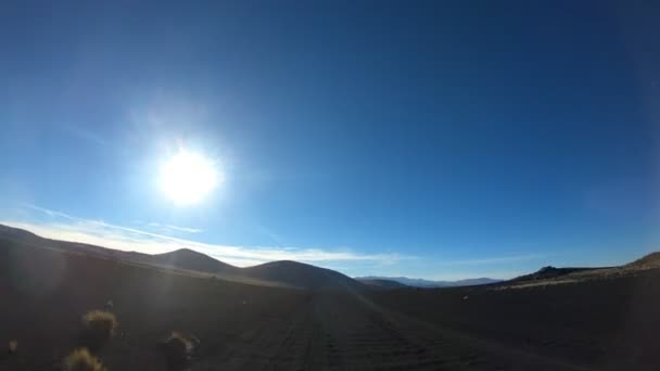 Timelapse at La Payunia National Park in Malarge, Cuyo, Mendoza. Camera gripped at car moving forward on gravel black volcanic road rocks and golden grasses. Volcanos on background.