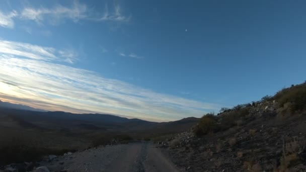 Stabilized camera movement gripped on a car at sunset golden hour. The Andes mountains on background. Van descending from mountains. Small shrubs on the sides of the gravel road. Mendoza, Argentina.