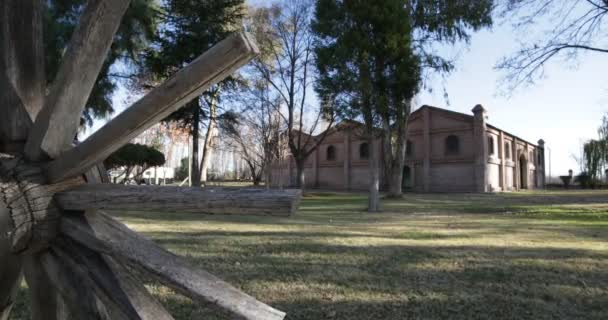 Traveling and panning perfect camera motion of big brick construction at sunset golden hour. Old wooden vintage cart wagon wheel. Trees, leaves and grass. Cellar for wine production in Mendoza, Argentina.