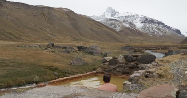 Young man taking a natural healthy hot thermal exterior bath at Cajon Grande watching The Campanario mountain at The Andes with snow in winter on a cloudy day. Mendoza, Cuyo, Argentina.