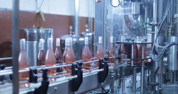 automatischer Weinflaschenverschluss. Detail von Glasflaschen, die mit grauen Kapseln verschlossen werden. effizientes, schnelles System. Kamera bleibt still. Getränkeindustrie.