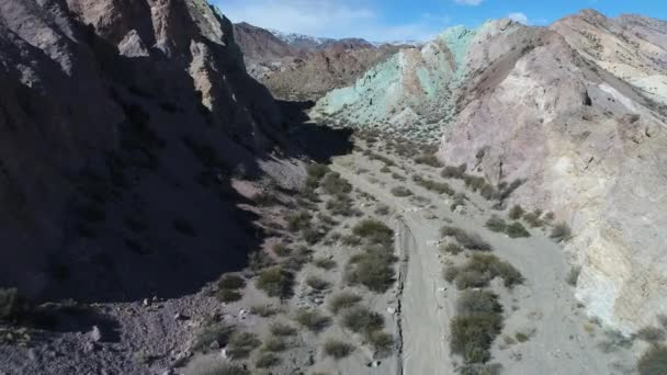 Aerial drone scene of colourful sandy and rocky mountains. Traveling along dry river towards blue hill, passing above mountain in Uspallata, Mendoza, Argentina.