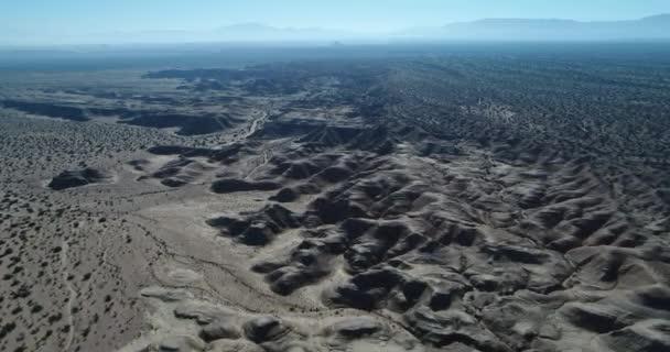 Légi drone jelenet, valamint a geológiai képződmények, erodált sandrock hegyek, vízmosások, a Nemzeti Park Talampaya, Világörökség, La Rioja. Kamera mozog előre. Nagy hegyek a háttérben.