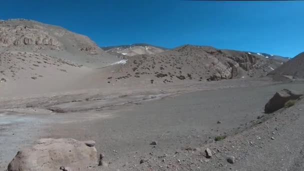 Traveling beside desertic valley of Desaguadero River. High rocky, snowy hills at background. Excursion to Brava Lagoon at The Andes. Rioja Province, Argentina