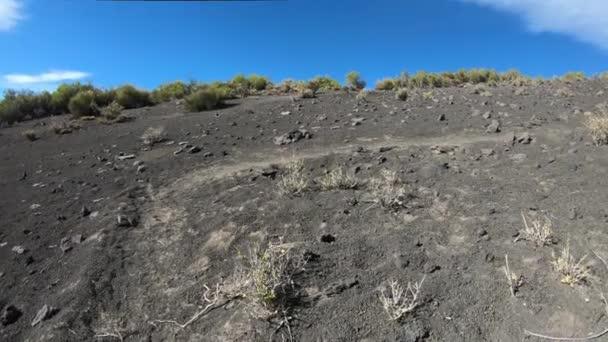 Pěšky přes vulkanické půdě, trosky, směrem k malacara sopka. Cestování přes štěrk stezka. Pozadí mountian. Mendoza, Argentina.