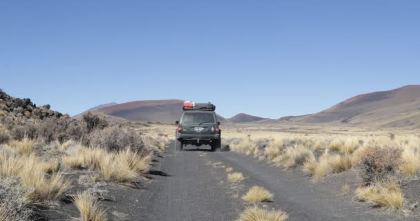 Van in Payunia National Park. Volcanic zone made of lapillis. Background of Herradura Volcano and red, black and golden mountains. Camera stays still while car moves. Malarge, Mendoza, Argentina