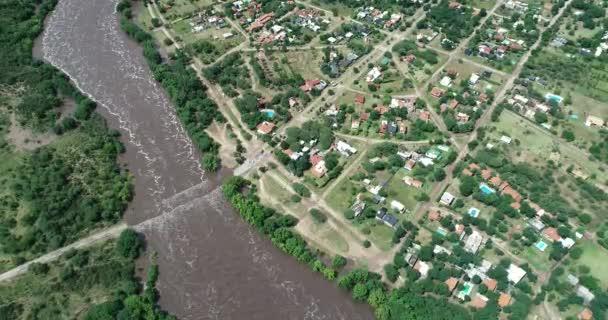 Aerial senital drone scene of wide brown strong river flowing and growing towards rural city, water flowing over bridge. Flood in Mina clavero, traslasierra, Corodoba, argentina