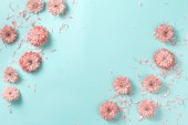 Flowers composition with flowers and petals  on a pastel pink background