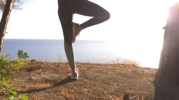 Woman fitness runner on top happy and celebrating success. the woman enjoys the view of the sea from the mountain, she raises her hands up and feels the freedom and breath of the wind. 4k, slow motion
