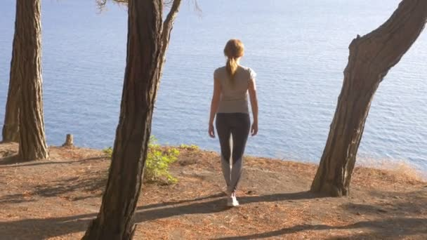 Woman fitness runner on top happy and celebrating success. the woman enjoys the view of the sea from the mountain, she feels the freedom and breath of the wind. 4k, slow motion, sunlight, stedikam