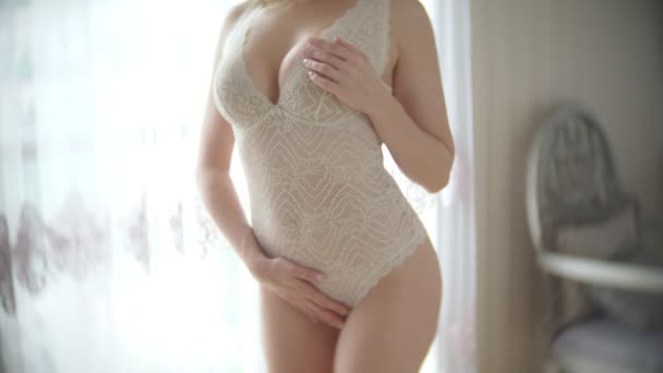 Pretty woman in beige body posing in seductive poses. in a room with an elegant interior. great slim body and big boobs. 4k