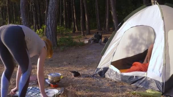 ženy, odpočívá, vaří jídlo vedle stanu na okraji strmého pobřeží v borovém háji s nádherným výhledem přímořská krajina. 4k.