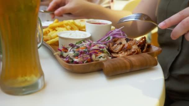 pár, jíst v venkovní kavárna řecká jídla, suvláki a pivo. 4k, pomalý pohyb