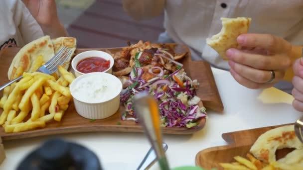 žena jí kavárna řecká jídla, souvlaki. detail z rukou. 4k, pomalý pohyb