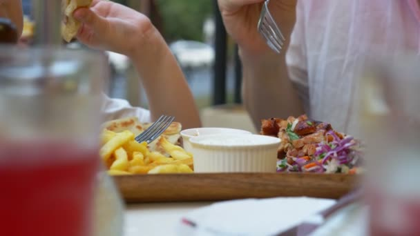 dad and his little daughter eating in an open-air cafe Greek dishes, souvlaki. close-up . 4k, slow motion