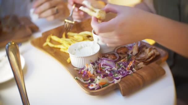 a couple, eating in an outdoor cafe Greek dishes, souvlaki and beer. 4k, slow motion