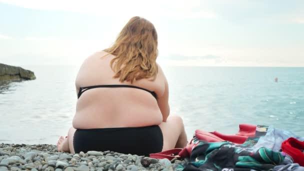 bb9db6798aa Ένα λίπος αγνώριστη γυναίκα κάθεται στην παραλία με την πλάτη στην κάμερα,  χαρούμενοι άνθρωποι είναι το ...