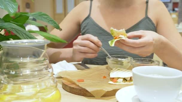 žena je jíst v café quesadilla s chilli a nachos. 4k, pomalý pohyb