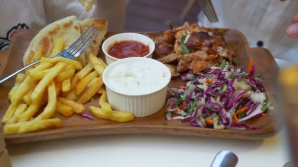 a woman is eating in an open-air cafe Greek dishes, souvlaki. close-up of hands. 4k, slow motion