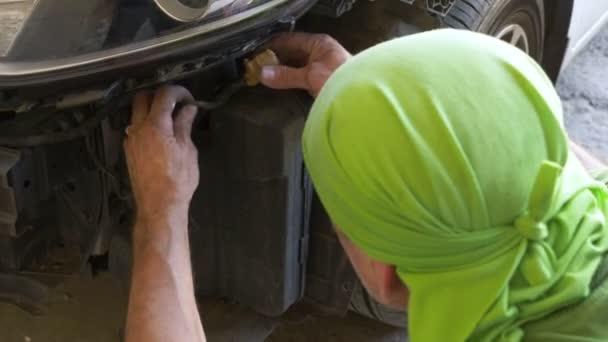Nahaufnahme. des Mechanikers, der die Stoßstange des Autos entfernt, repariert er das Auto. 4k