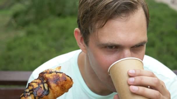 Ein gut aussehender Mann sieht glücklich beim Essen einer leckeren Croissants. Nahaufnahme der Lippen. 4 k-Slow-motion
