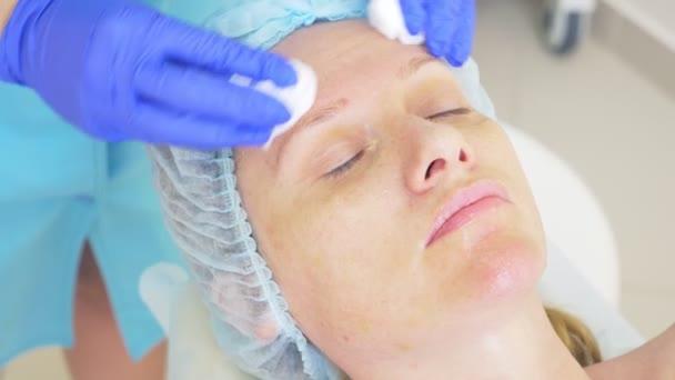 Nahaufnahme der Beauty-Prozedur. Kosmetikerin reinigt Gesichtsmaske. Peeling. Schönheits- und Körperpflege. Zeitlupe 4k