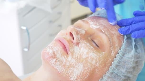 Közelről kozmetikai eljárás. Kozmetikus tisztító arcpakolás. Peeling. Szépség- és bőrápolás. lassú mozgás 4k