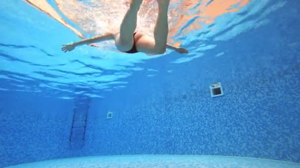 4k. View under water. Woman in a black swimsuit Swims in the pool.