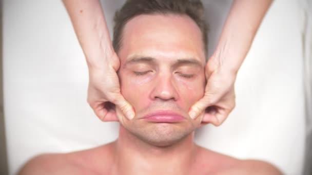 Az ember egyre arc masszázs. Masszázs az arc és a nyak. hazudik a kasmetologist hivatalban. 4k, lassú mozgású, felülnézet