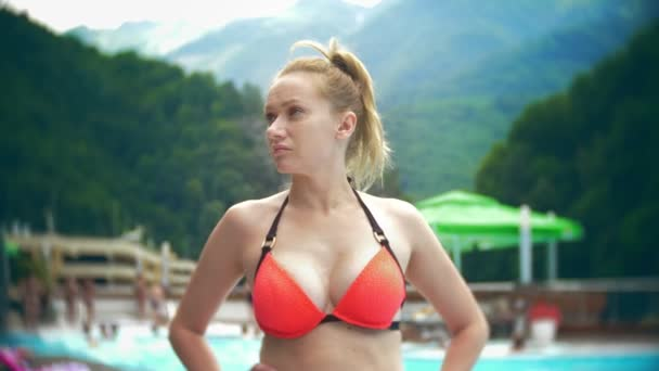 SLOW MOTION, CLOSE, PORTRAIT. young woman , sunbathe and relax on a sunny day in a luxurious pool on a background of a mountain landscape. mountain resort with outdoor pool. 4k