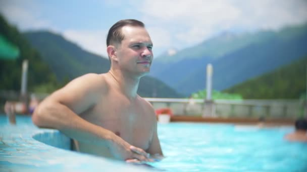 SLOW MOTION, CLOSE, PORTRAIT. young man sunbathe and relax on a sunny day in a luxurious pool on a background of a mountain landscape. mountain resort with outdoor pool. 4k