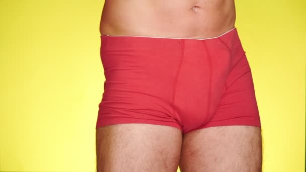 a man in red boxers dancing on a yellow background. close-up. 4k, slow motion
