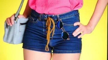 e70c16375496ed Een meisje in denim shorts met een mode-accessoire. Denim mesh en zonnebril  ronde