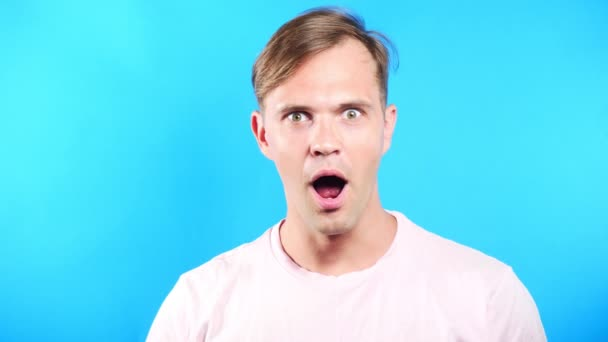 Young man on color blue background. portrait. emotions and gestures. 4k, close-up. Slow motion. surprise.