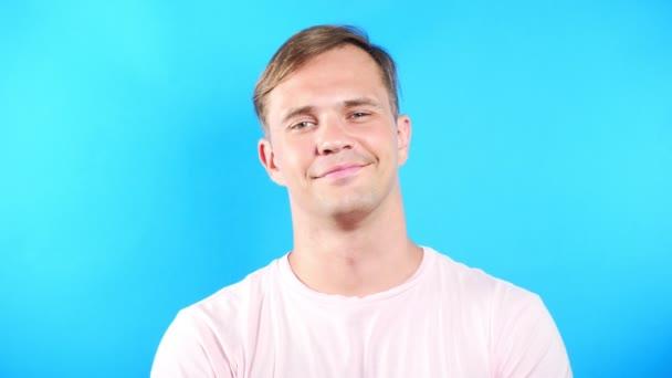 Mladý muž na barevném modrém pozadí. portrét. emoce a gesta. 4k, detail. Zpomalený pohyb. chlap se dívá na fotoaparát a roztomilý úsměv