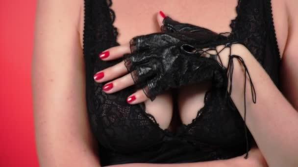 4k. Nahaufnahme. Zeitlupe. eine Frau mit großer Brust streichelt ihre Brust mit ihrer behandschuhten Hand