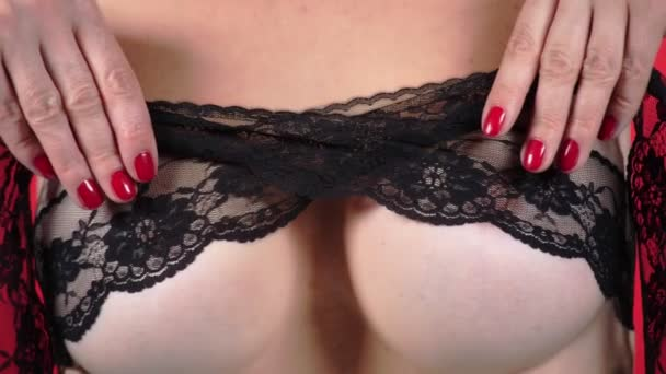 Oben ohne Schönheit Frauenkörper bedeckt ihre Brust. 4k. Nahaufnahme. Zeitlupe. eine Frau mit großen Brüsten streichelt ihre Brüste. schwarze Spitze.