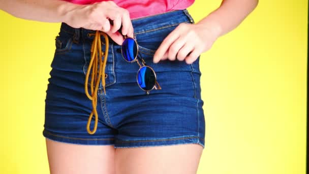 A girl in denim shorts with a fashion accessory. sunglasses round mirror glasses. Summer fresh style. colored yellow background